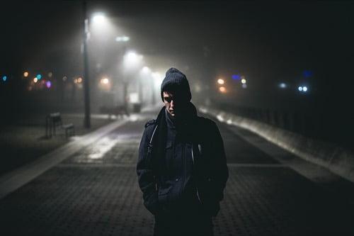 暗い道を歩く男性